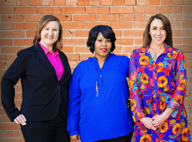 denson dental team standing together behind brick wall